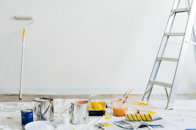 Secchi di pittura e scala con rulli per dipingere le pareti